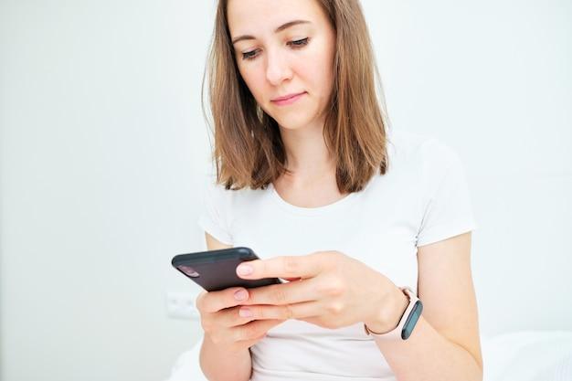 Młoda kobieta kaukaski używa telefonu w domu