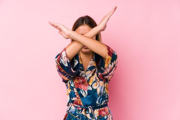 Młoda kobieta kaukaski w piżamie, trzymając skrzyżowane ręce, koncepcja odmowy.