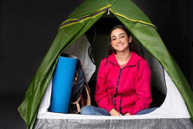 Młoda kobieta kaukaski wewnątrz zielonego namiotu kempingowego, pozowanie z rękami na biodrze i uśmiechnięty