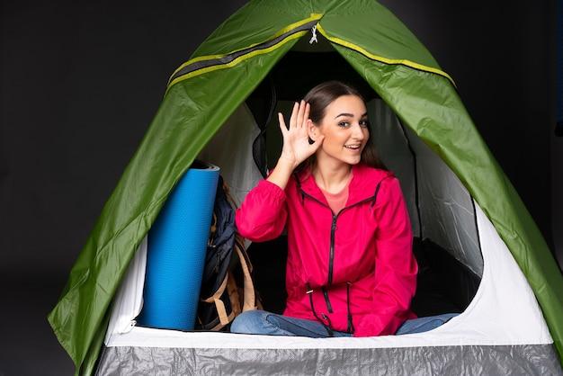 Młoda kobieta kaukaski wewnątrz zielonego namiotu kempingowego, słuchając czegoś