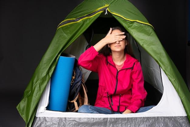 Młoda kobieta kaukaski wewnątrz zielonego namiotu kempingowego, zasłaniając oczy rękami. nie chcę czegoś zobaczyć