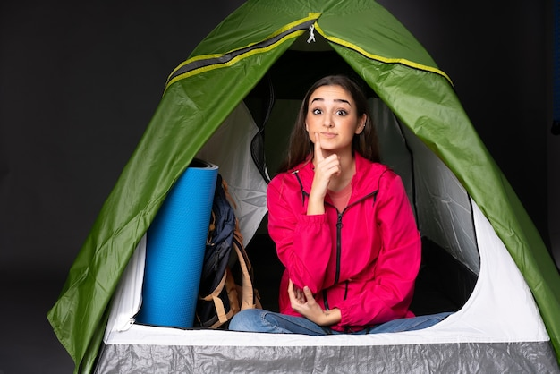 Młoda kobieta kaukaski wewnątrz zielonego namiotu kempingowego