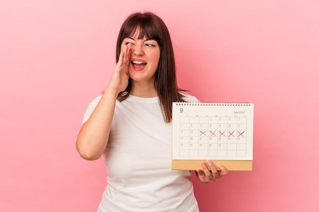 Młoda kobieta kaukaski z nadwagą trzyma kalendarz na białym tle na różowym tle krzycząc i trzymając dłoń w pobliżu otwartych ust.