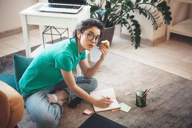 Młoda kobieta kaukaski z okularami, odrabiania lekcji na podłodze i jedzenie jabłka