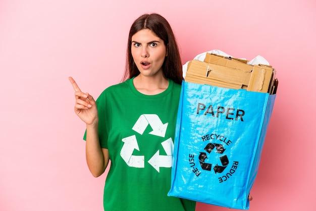 Młoda kobieta kaukaski z recyklingu kartonu na białym tle na różowym tle, wskazując w bok