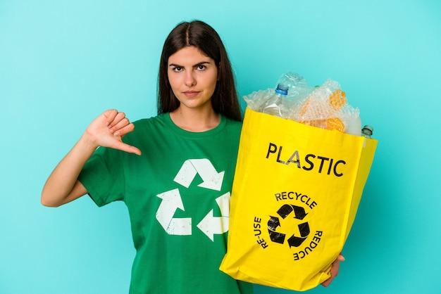 Młoda kobieta kaukaski z recyklingu plastiku na białym tle na niebieskim tle, pokazując gest niechęci, kciuk w dół. pojęcie sporu.