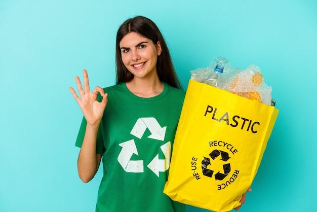 Młoda kobieta kaukaski z recyklingu plastiku na białym tle na niebieskim tle wesoły i pewny siebie, pokazując ok gest.