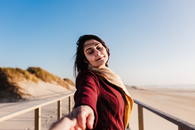 Młoda kobieta kaukaski z zamkniętymi oczami, relaks na plaży o zachodzie słońca.