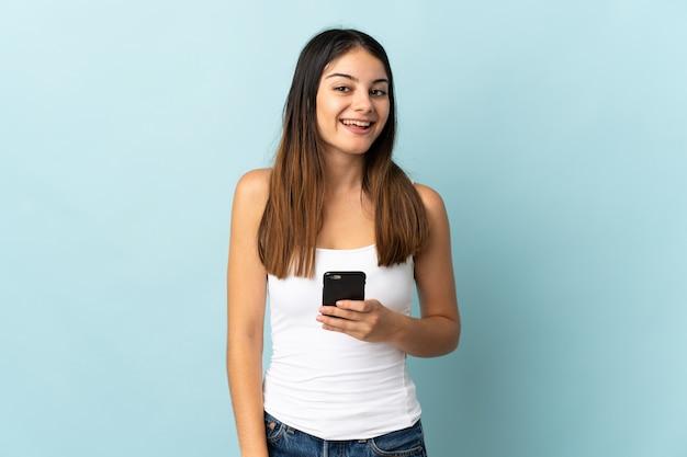 Młoda kobieta kaukaski za pomocą telefonu komórkowego na białym tle na niebiesko z zaskoczeniem wyraz twarzy