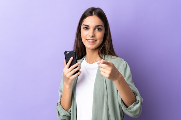Młoda kobieta kaukaski za pomocą telefonu komórkowego na fioletowych punktach palcem na ciebie z pewną siebie