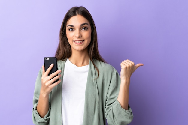 Młoda kobieta kaukaski za pomocą telefonu komórkowego samodzielnie na fioletowo, wskazując na bok, aby przedstawić produkt