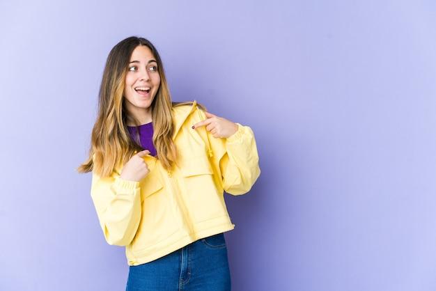 Młoda kobieta kaukaski zaskoczony, wskazując palcem, uśmiechając się szeroko.