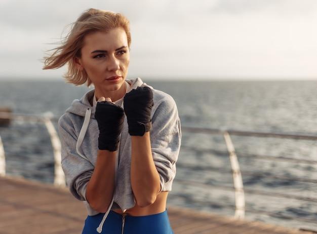 Młoda kobieta kickboxer w sportowej z zawiniętymi rękami w bandaże pociągi na plaży o wschodzie słońca