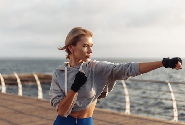 Młoda kobieta kickboxer z rękami owiniętymi w bandaże trenuje cios na plaży o wschodzie słońca