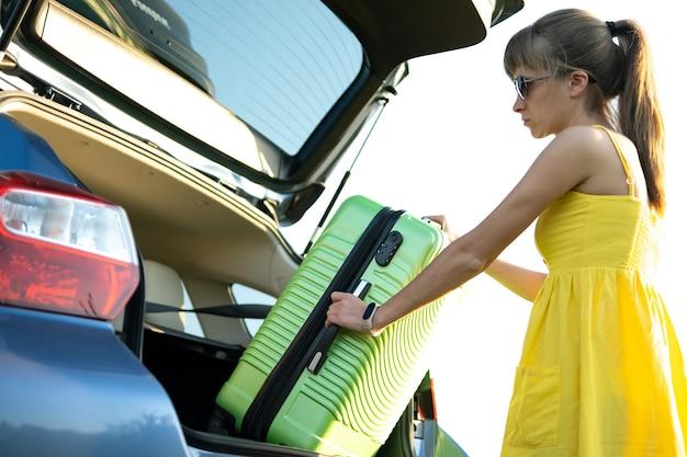Młoda kobieta kierowca biorąc zieloną walizkę z bagażnika samochodu. koncepcja podróży i wakacji.