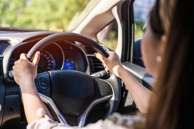 Młoda kobieta kierowca, koncentrując się na długiej podróży