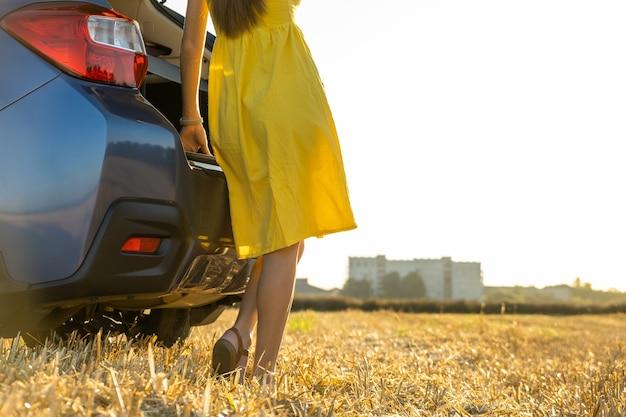 Młoda kobieta kierowca nogi w żółtej letniej sukience stojący w pobliżu jej samochodu, ciesząc się ciepłym letnim dniem o zachodzie słońca.