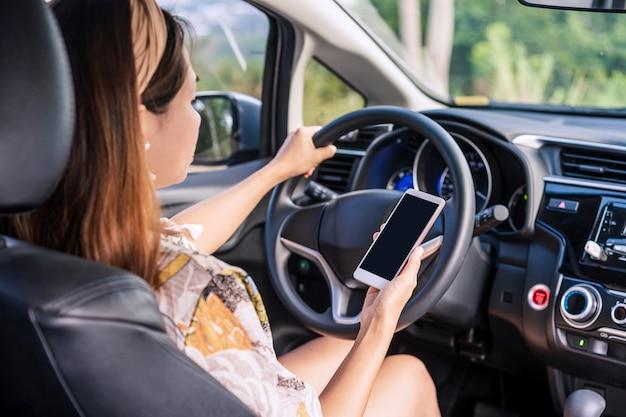 Młoda kobieta kierowca posiadający inteligentny telefon z miejsca na kopię podczas jazdy, co wskazuje na zaniedbanie