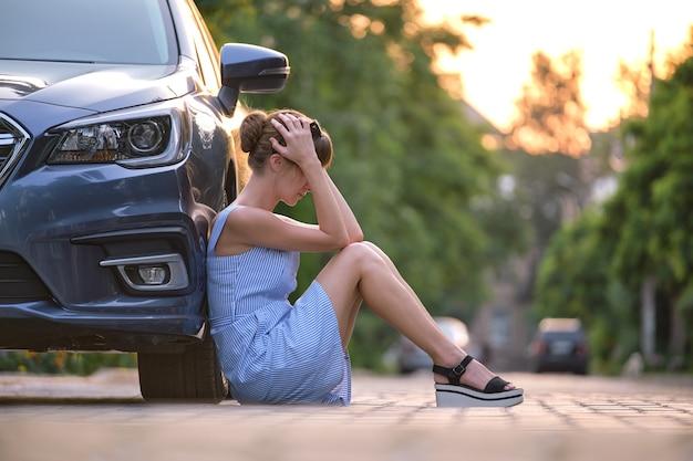 Młoda kobieta kierowca siedzi obok jej zepsutego samochodu, czekając na pomoc. koncepcja problemów z pojazdem.