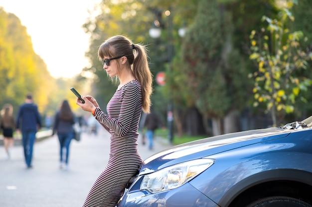 Młoda kobieta kierowca stojący w pobliżu jej samochodu rozmawia przez telefon komórkowy na ulicy miasta w lecie.