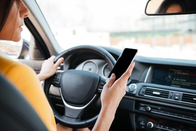 Młoda kobieta kierowca używa ekranu dotykowego smartphone