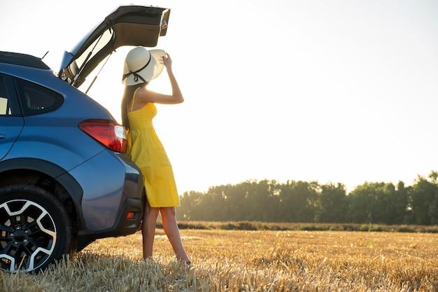 Młoda kobieta kierowca w żółtej letniej sukience i słomkowy kapelusz stojący w pobliżu samochodu, ciesząc się ciepłym letnim dniem o zachodzie słońca.
