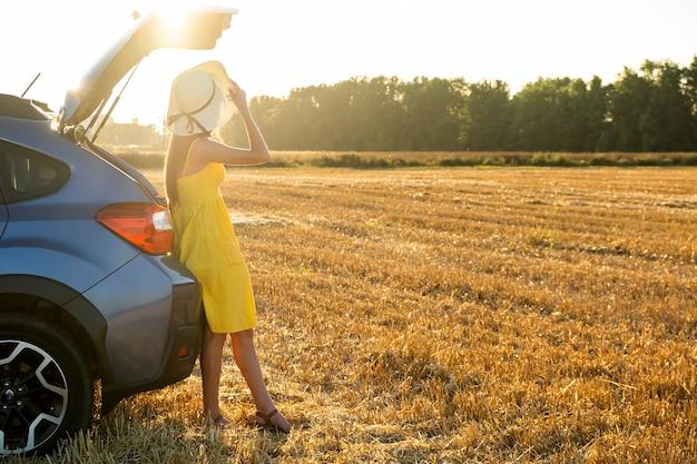 Młoda kobieta kierowca w żółtej letniej sukience i słomkowym kapeluszu stojący obok jej samochodu