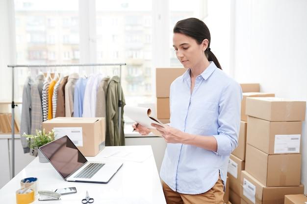 Młoda kobieta kierownik czytania notatek w notatniku podczas przygotowywania towarów do pakowania przez miejsce pracy