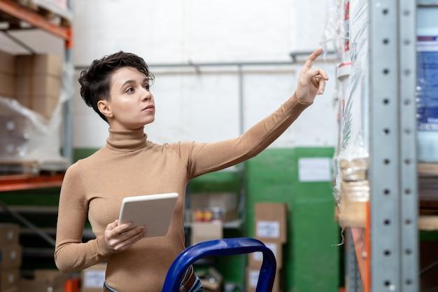 Młoda kobieta kierownik ds. logistyki z tabletem stojącym przy stojaku
