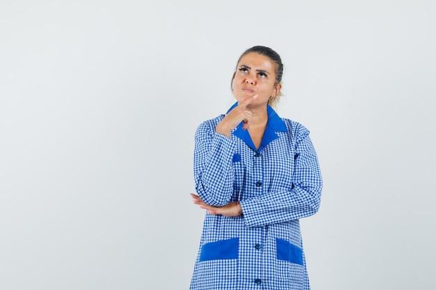 Młoda kobieta kładąc palec wskazujący na brodzie, stojąc w myśleniu gest w niebieskiej koszuli piżamy bawełniany materiał w kratkę i patrząc zamyślony. przedni widok.