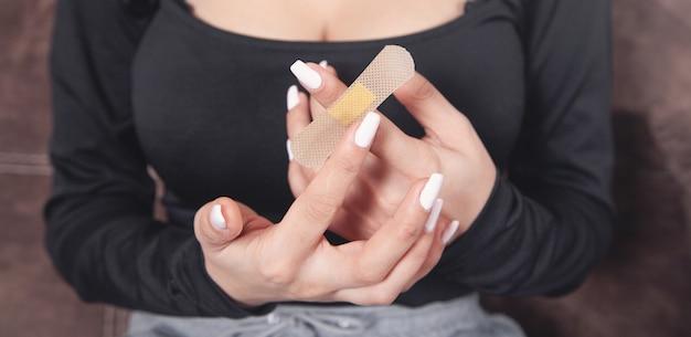 Młoda kobieta kładzenie klej bandaż w palcu.