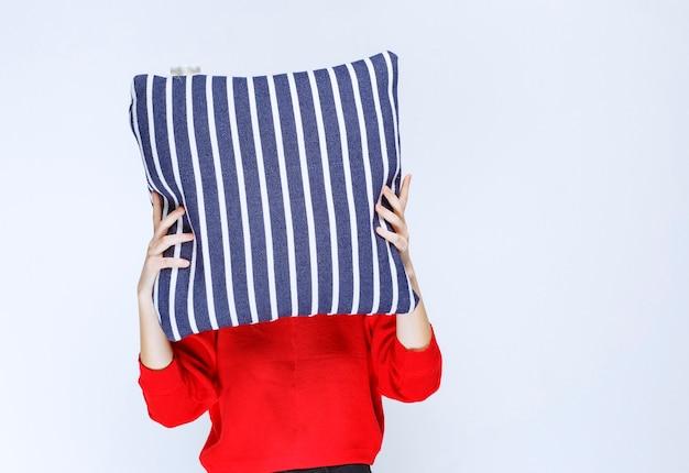 Młoda kobieta kładzie na twarz poduszkę w niebieskie paski.