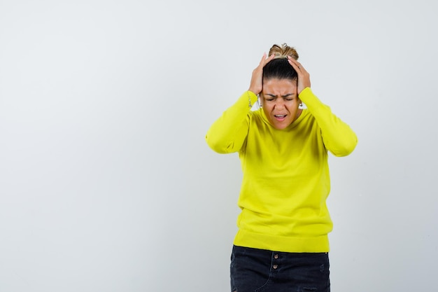 Młoda kobieta kładzie ręce na głowie, ma szeroko otwarte usta w żółtym swetrze i czarnych spodniach i wygląda na zmęczoną