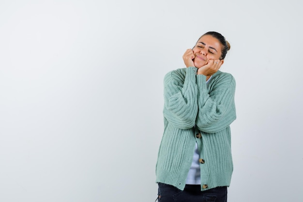 Młoda kobieta kładzie ręce na policzku, zamyka oczy w białej koszuli i miętowozielonym swetrze i wygląda na szczęśliwą