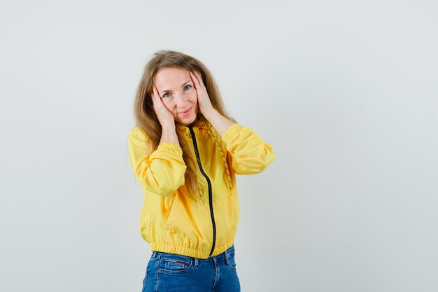 Młoda kobieta kładzie ręce na twarzy w żółtej bomberki i dżinsach i wygląda uroczo, widok z przodu.
