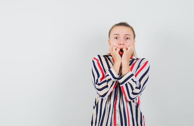 Młoda kobieta kładzie ręce na ustach w bluzce w paski i wygląda zszokowana
