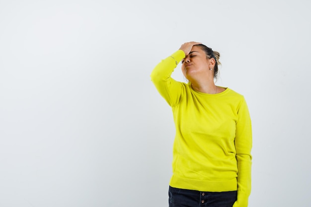 Młoda kobieta kładzie rękę na czole, ma ból głowy w żółtym swetrze i czarnych spodniach i wygląda na zmęczoną