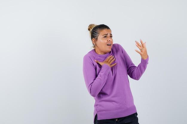 Młoda kobieta kładzie rękę na klatce piersiowej i wygląda na zaskoczoną