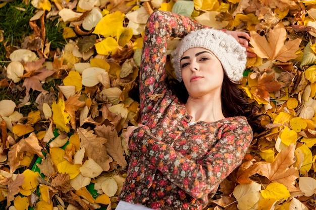 Młoda kobieta kłaść w jesień liściach