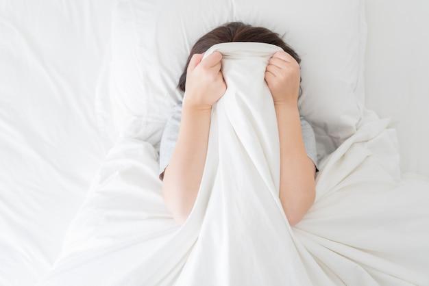 Młoda kobieta kłaść w łóżku chuje jej twarz