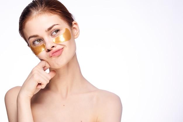 Młoda kobieta klei plamy pod oczami