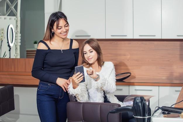 Młoda kobieta klientka robi fryzurę i stylizację u profesjonalnego fryzjera w salonie kosmetycznym