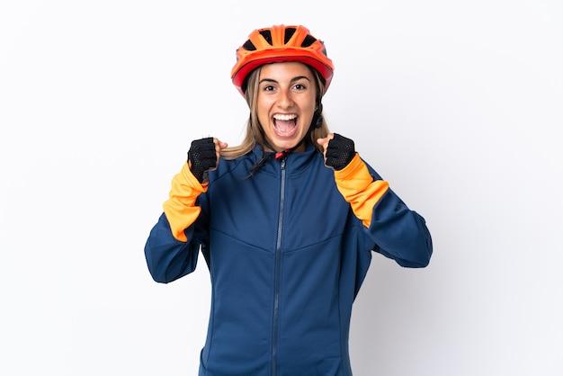 Młoda kobieta kolarz hiszpanin samodzielnie na białej ścianie świętuje zwycięstwo w pozycji zwycięzcy