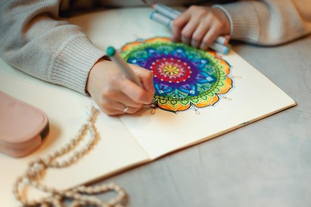 Młoda kobieta kolorowania mandali z markerami
