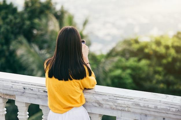 Młoda kobieta koloru żółtego suknia patrzeje z smartphone przy podziwiać widok górę.