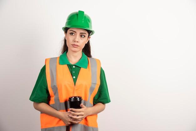 Młoda kobieta konstruktor trzymając czarny kubek i odwracając. zdjęcie wysokiej jakości