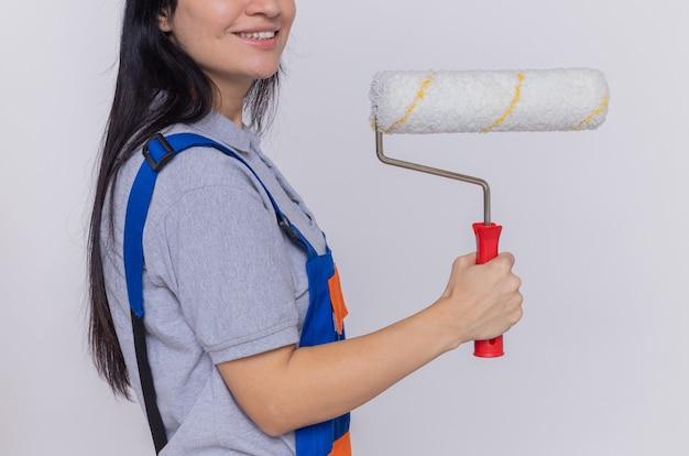 Młoda kobieta konstruktora w mundurze budowy gospodarstwa wałek do malowania stojący nad białą ścianą