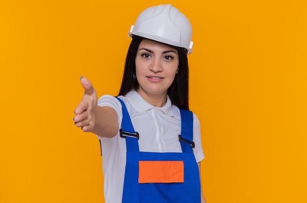 Młoda kobieta konstruktora w mundurze budowy i hełmie ochronnym patrząc na przód uśmiechnięty pewny siebie, oferując gest powitania ręki stojącej nad pomarańczową ścianą