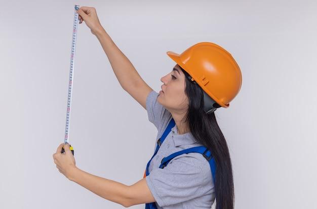 Młoda kobieta konstruktora w mundurze budowy i hełmie ochronnym patrząc na środek taśmy z poważną twarzą stojącą na białej ścianie