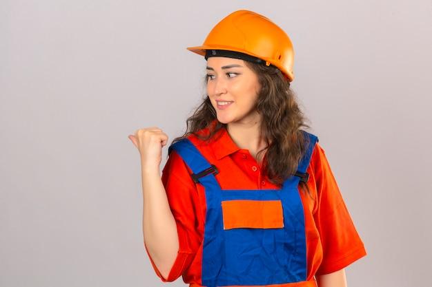 Młoda kobieta konstruktora w mundurze budowy i hełmie ochronnym, uśmiechając się ze szczęśliwą twarzą, patrząc i wskazując na bok z kciukiem do góry nad izolowaną białą ścianą